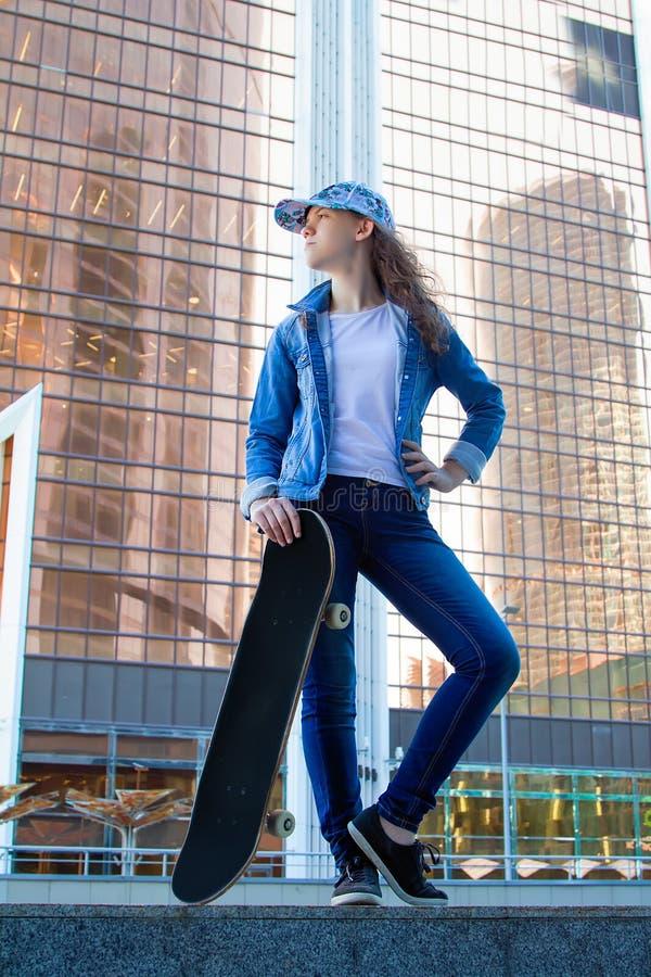 Une jeune fille dans des vêtements de denim se tient avec un patin sur le fond d'un gratte-ciel photos stock