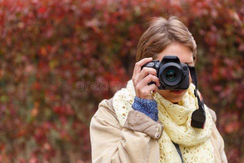 Une jeune fille dans une forêt d'automne avec un appareil-photo images libres de droits