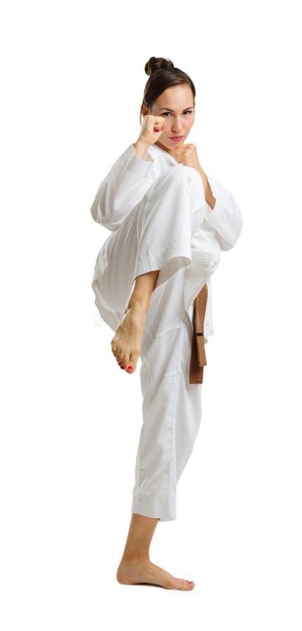 Une jeune fille dans une pose de karaté D'isolement sur le fond blanc image stock
