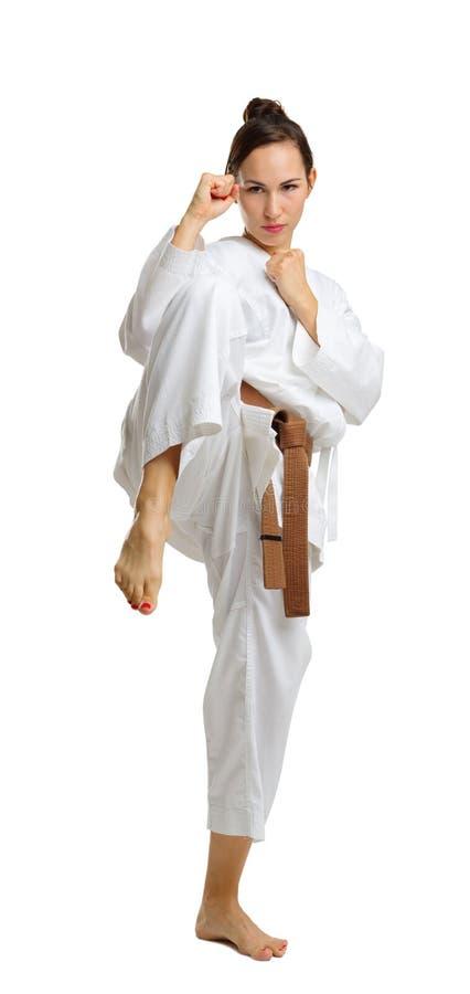 Une jeune fille dans une pose de karaté D'isolement sur le fond blanc images stock