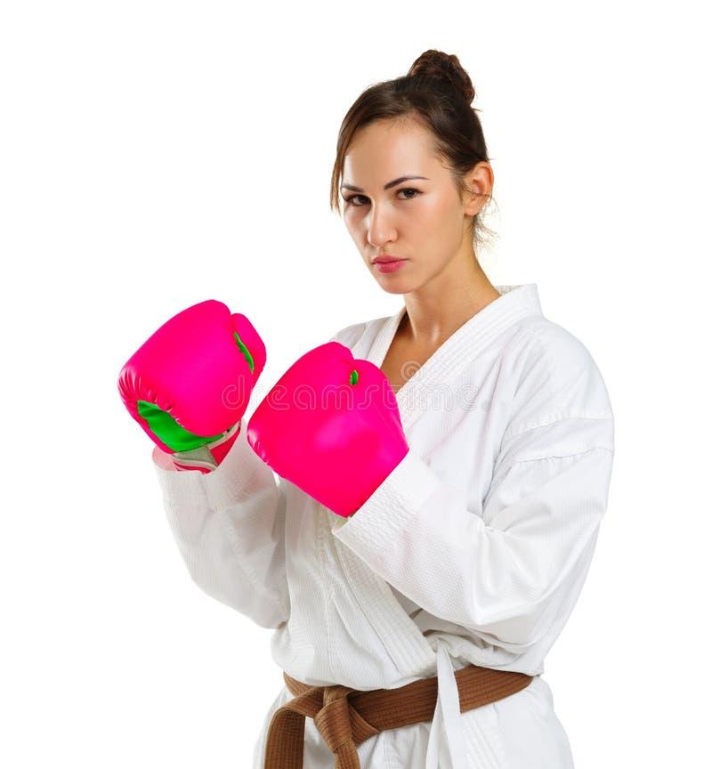 Une jeune fille dans une pose de karaté Dans les gants roses D'isolement sur le fond blanc photographie stock libre de droits