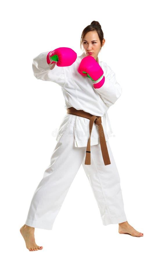Une jeune fille dans une pose de karaté Dans les gants roses D'isolement sur le fond blanc images libres de droits