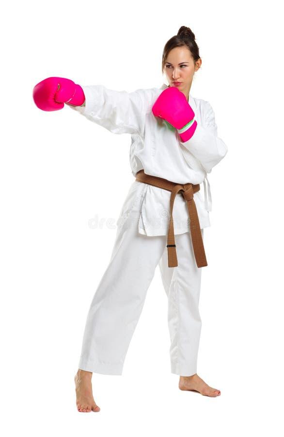 Une jeune fille dans une pose de karaté Dans les gants roses D'isolement sur le fond blanc image stock