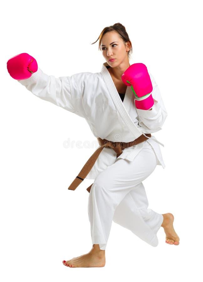 Une jeune fille dans une pose de karaté Dans les gants roses D'isolement sur le fond blanc photo libre de droits