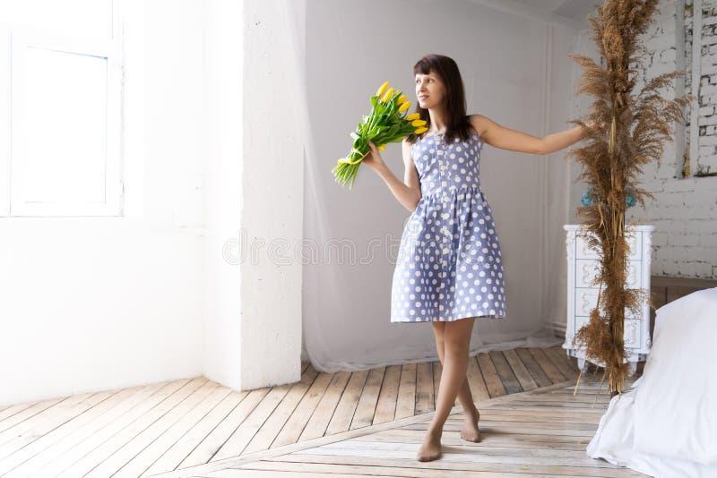 Une jeune fille dans une robe bleue se tient prêt le lit dans une salle blanche spacieuse et inhale le parfum d'un grand bouquet  photographie stock libre de droits