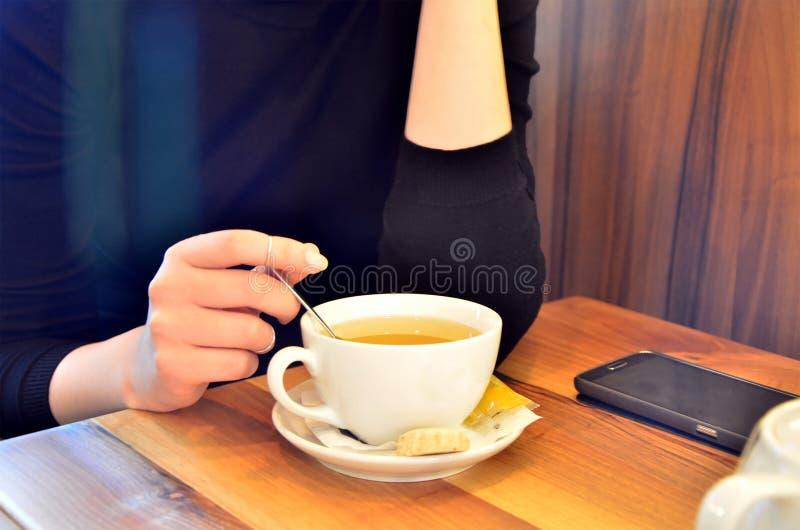 Une jeune fille dans un café boit du thé image stock