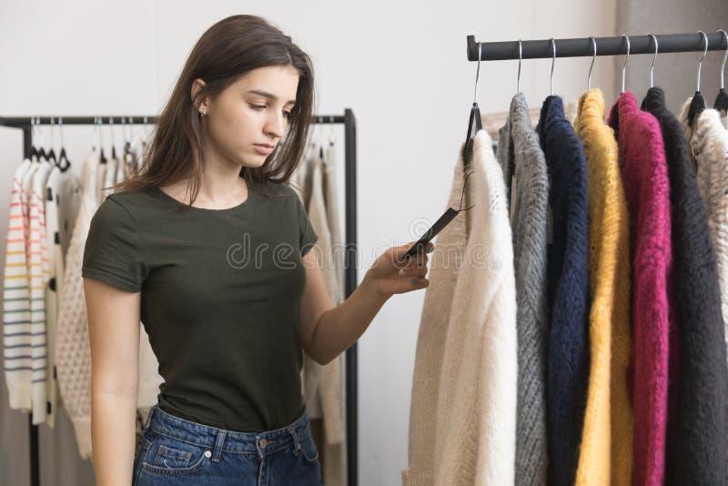 Une jeune fille dans un magasin d'habillement, choisit un chandail photo libre de droits