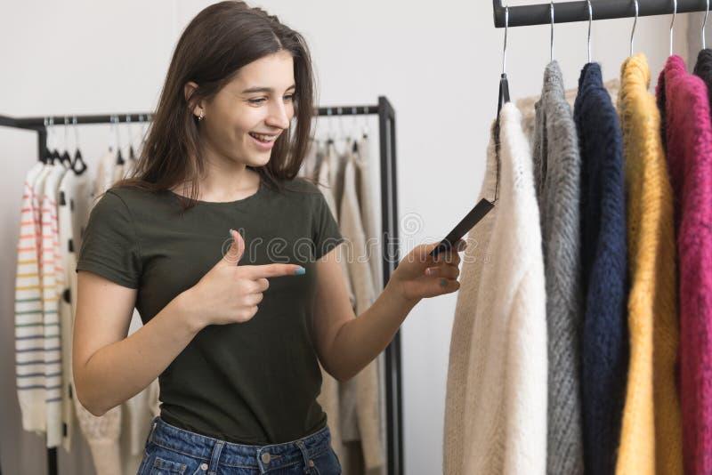 Une jeune fille dans un magasin d'habillement, choisit un chandail photos stock