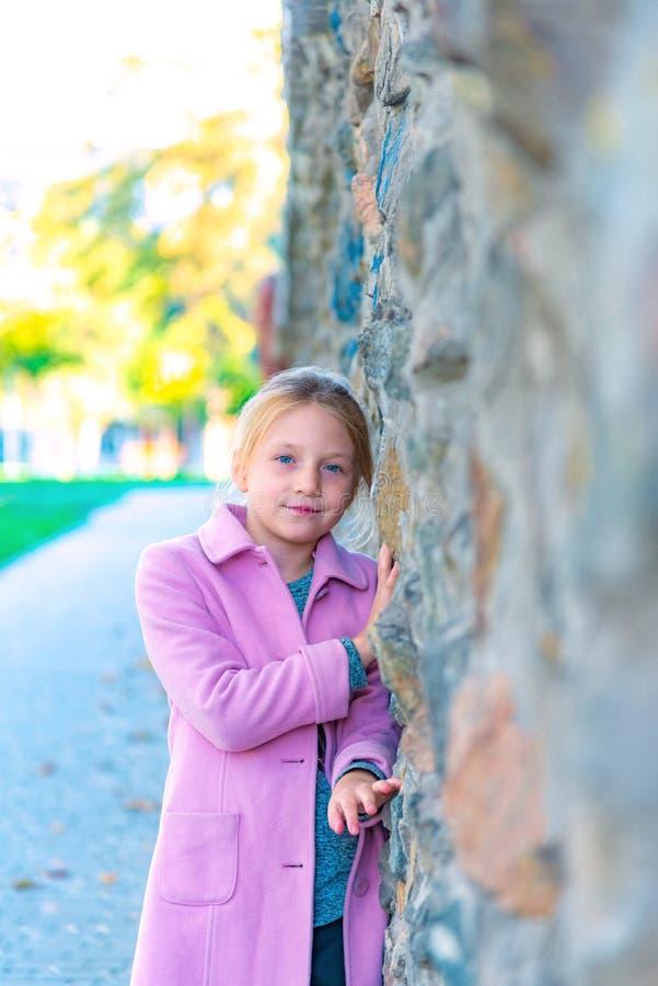 Une jeune fille dans un manteau rose se penche contre un mur, frottant dans la fin  image libre de droits