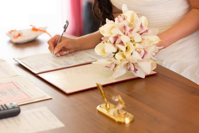 Une jeune fille dans une robe de mariage a signé un document important images stock