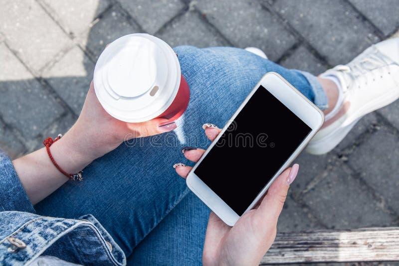 Une jeune fille dans une veste de denim descend la rue avec du café et un téléphone dans des ses mains Fille dans les verres et u image libre de droits
