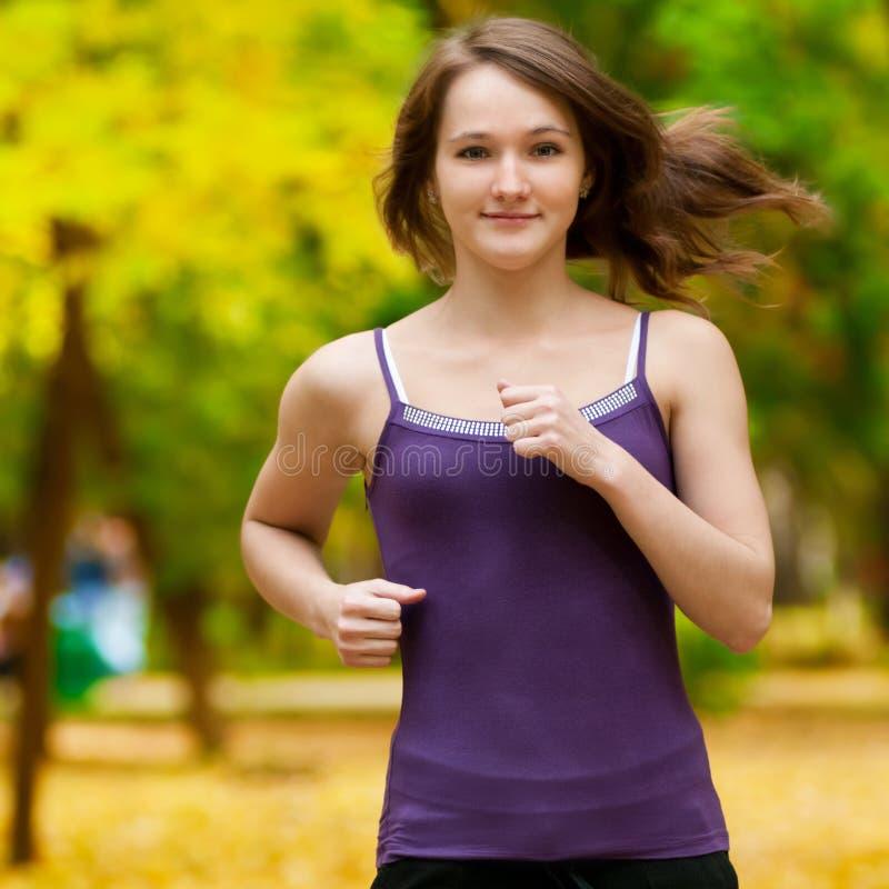 Une jeune fille exécutant en stationnement d'automne photos libres de droits