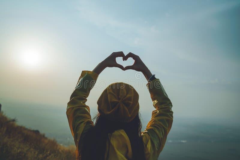 Une jeune fille faisant le symbole de coeur avec ses mains au coucher du soleil photos libres de droits