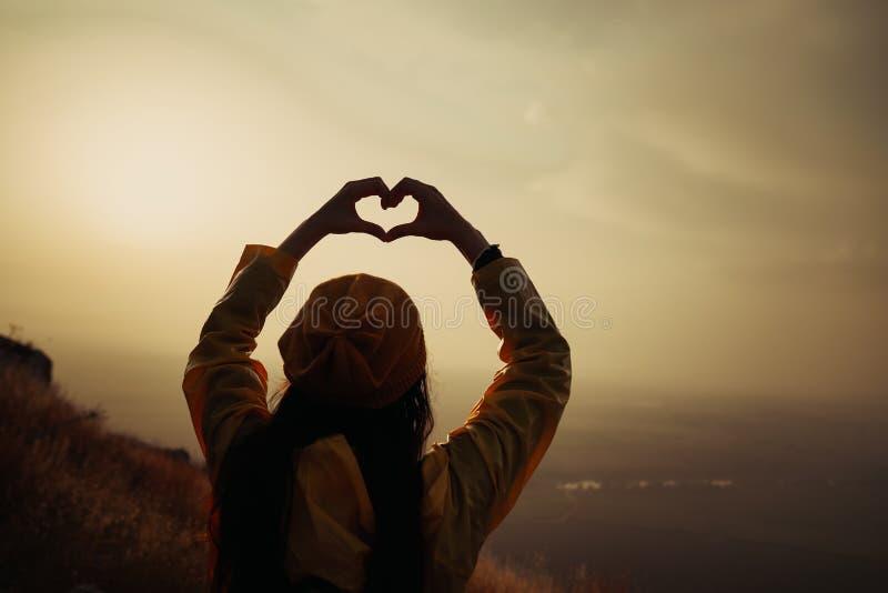 Une jeune fille faisant le symbole de coeur avec ses mains au coucher du soleil image stock