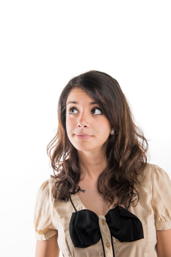 Une jeune fille habillée dans une chemise brune et un arc regarde en longueur avec un visage douteux images stock
