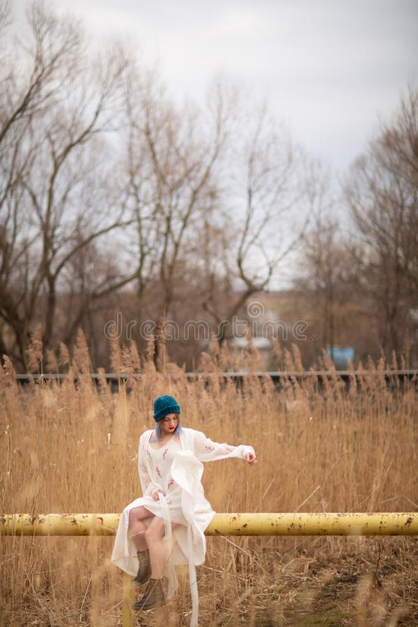 Une jeune fille habill?e dans une longue robe blanche, se reposant sur un tuyau, pr?s d'un champ de bl photos libres de droits