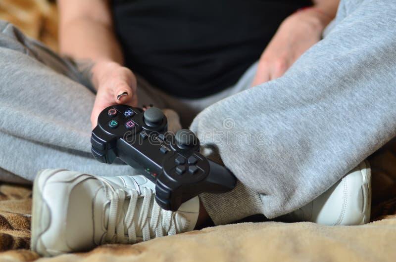 Une jeune fille joue des jeux vidéo avec une manette noire avec des beaucoup b photo libre de droits