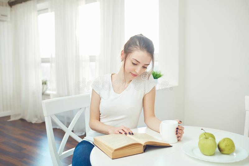 Une jeune fille lit un livre se reposant à une table images libres de droits