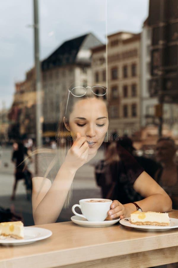 Une jeune fille mange un gâteau et boit du café dans un café photographie stock
