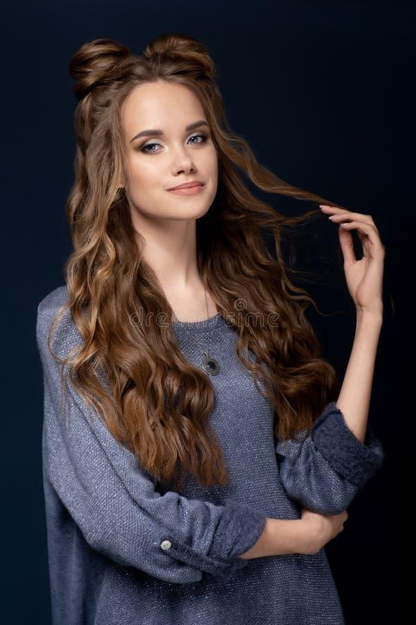 Une jeune fille mignonne dans une robe tricotée bleue sur un fond bleu avec une coupe de cheveux et de longs cheveux bouclés images stock