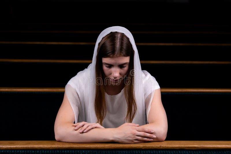 Une jeune fille modeste avec un mouchoir sur sa tête s'assied dans l'église et la prière Le concept de la religion, prière, culte photographie stock libre de droits