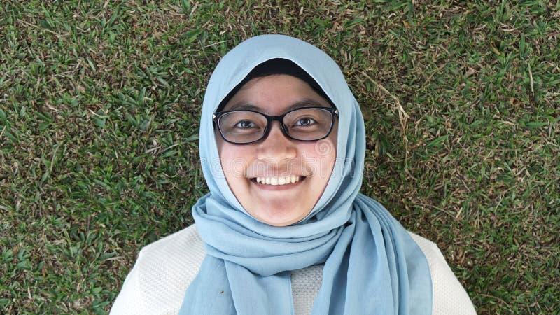 Une jeune fille musulmane s'étendant sur l'herbe verte photos libres de droits