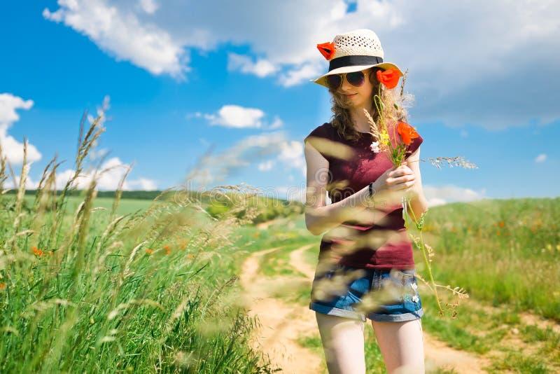 Une jeune fille plume des fleurs d'un pavot photos libres de droits