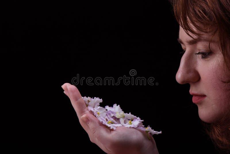 Une jeune fille regarde les fleurs du Saintpaulia violet sur la paume Concept de soin de peau image libre de droits