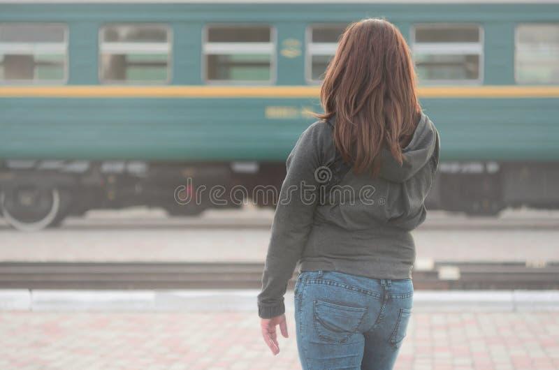 Une jeune fille rousse se tient sur la plate-forme ferroviaire et observe le train de départ La femme était en retard pour son tr image stock