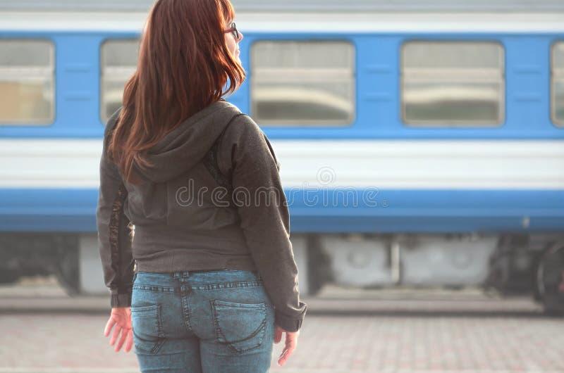 Une jeune fille rousse se tient sur la plate-forme ferroviaire et observe le train de départ La femme était en retard pour son tr photo libre de droits