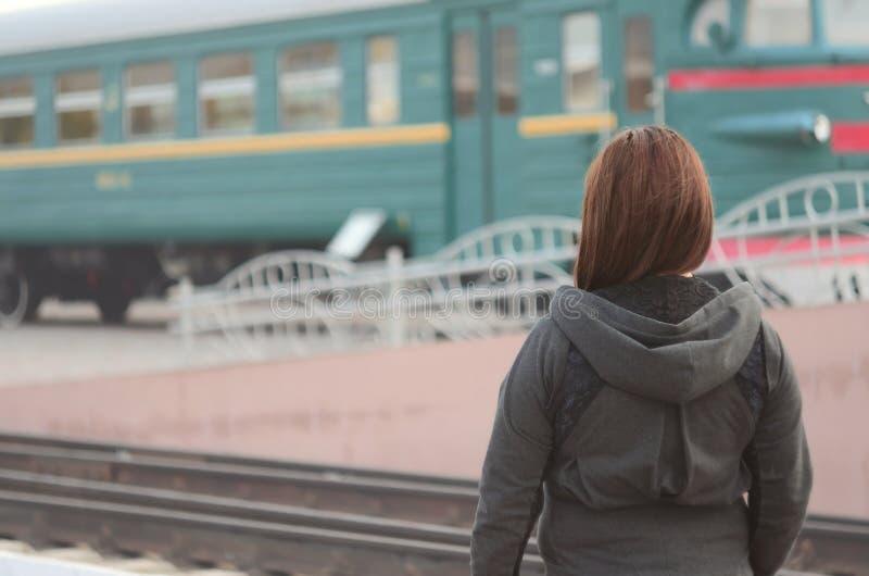 Une jeune fille rousse se tient sur la plate-forme ferroviaire et observe le train de départ La femme était en retard pour son tr photographie stock libre de droits