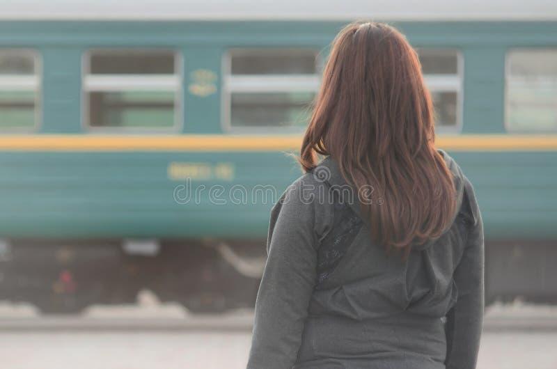 Une jeune fille rousse se tient sur la plate-forme ferroviaire et observe le train de départ La femme était en retard pour son tr photographie stock