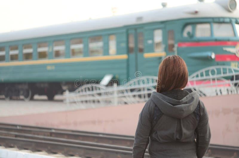 Une jeune fille rousse se tient sur la plate-forme ferroviaire et observe le train de départ La femme était en retard pour son tr photos stock