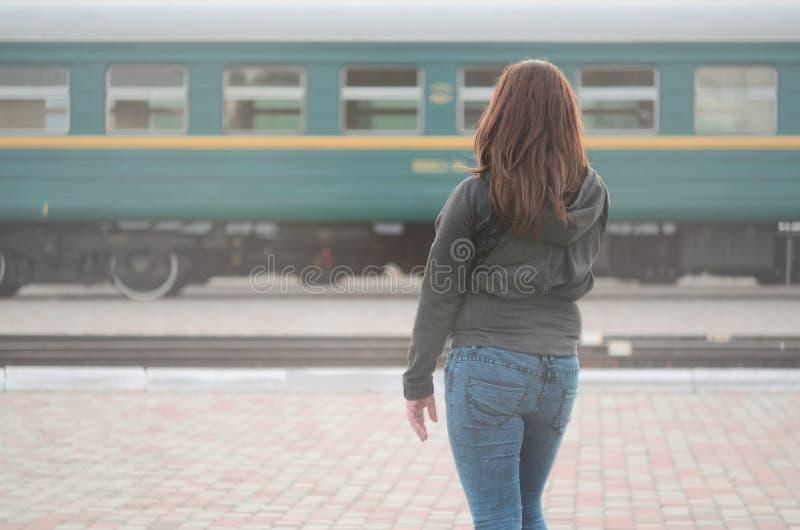 Une jeune fille rousse se tient sur la plate-forme ferroviaire et observe le train de d?part La femme ?tait en retard pour son tr images stock