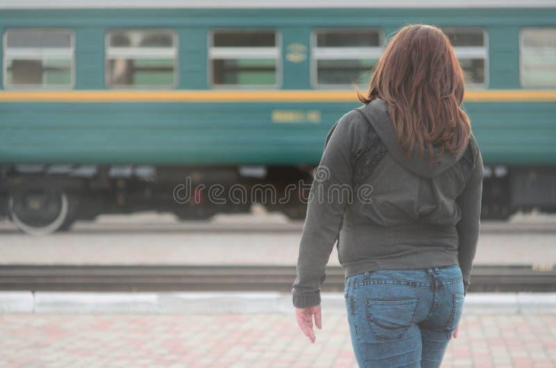 Une jeune fille rousse se tient sur la plate-forme ferroviaire et observe le train de d?part La femme ?tait en retard pour son tr image libre de droits