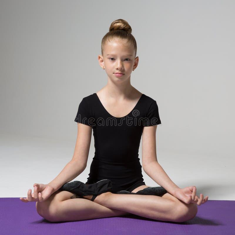 Une jeune fille s'assied dans une pose de lotus méditation Enfant photo stock