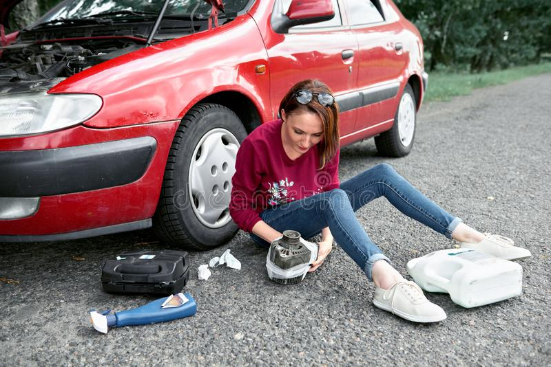 Une jeune fille s'assied près d'une voiture cassée et dépanne au générateur électrique, à côté de elle là sont de mauvaises pièce photo stock