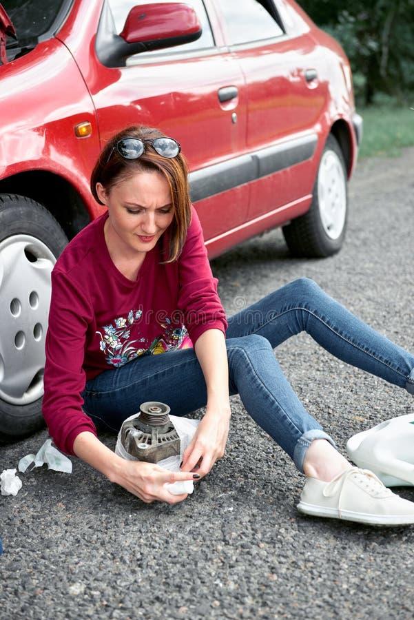 Une jeune fille s'assied près d'une voiture cassée et dépanne au générateur électrique, à côté de elle là sont de mauvaises pièce image libre de droits