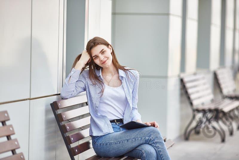 Une jeune fille s'assied sur un banc avec un comprimé dans ses mains et sourire image libre de droits