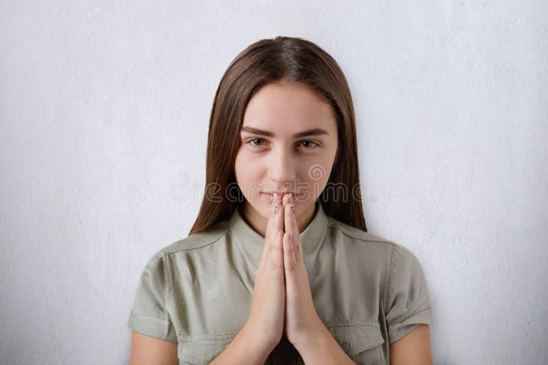 Une jeune fille sûre avec de beaux yeux foncés et les cheveux priant avec ses mains ensemble sur le fond gris ayant croient au be images libres de droits