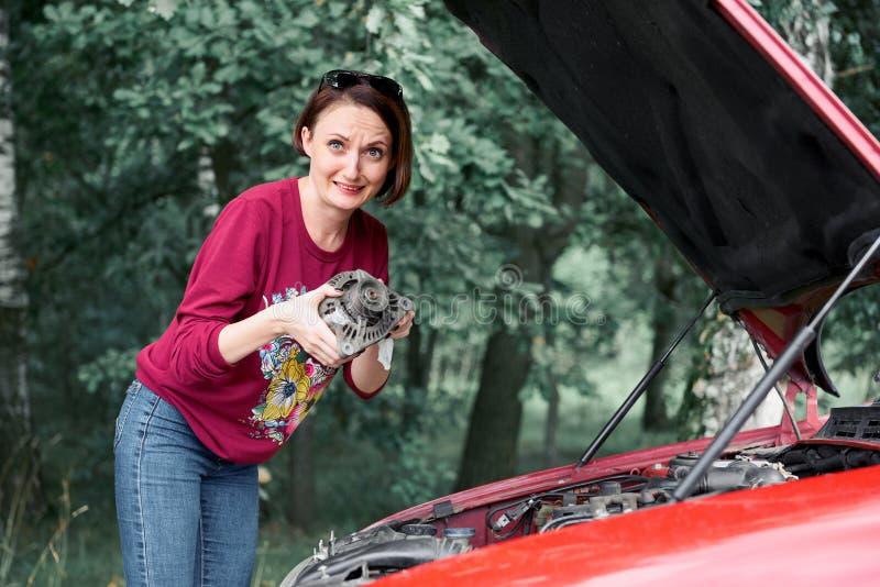 Une jeune fille se tient à une voiture cassée et tient une mauvaise pièce de rechange, un générateur électrique, ne comprend pas  photographie stock