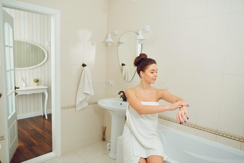 Une jeune fille se tient dans une serviette dans la salle de bains images libres de droits