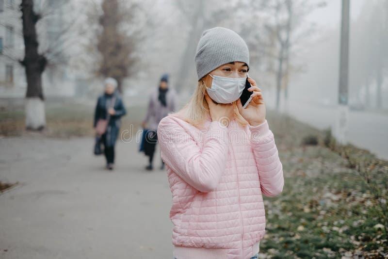 Une jeune fille se tient près de la route avec un masque médical Protection contre une épidémie de virus dans une ville image libre de droits