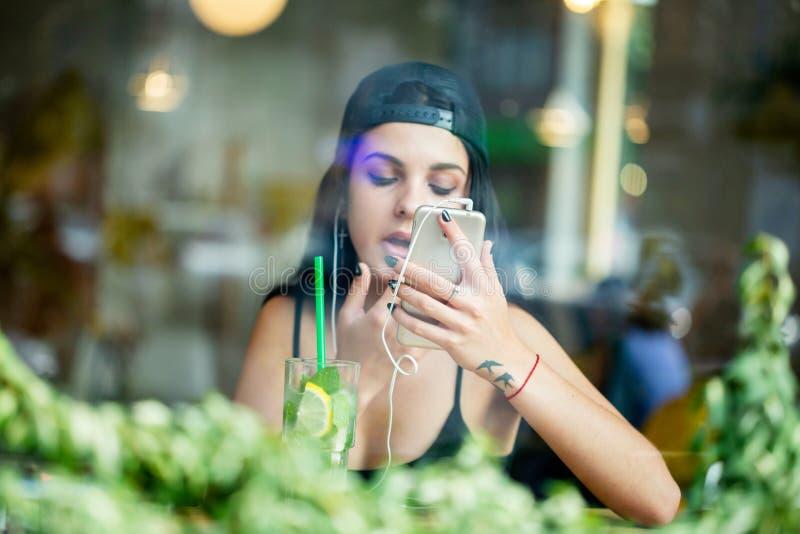 Une jeune fille seul s'assied dans un café, écoute la musique sur des écouteurs et vérifie le maquillage par le smartphone d'a photographie stock