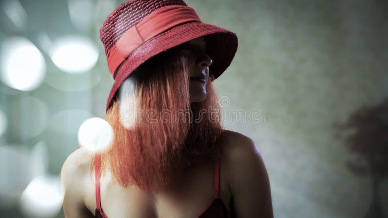 Une jeune fille sexy avec les cheveux rouges dans le chapeau photographie stock libre de droits