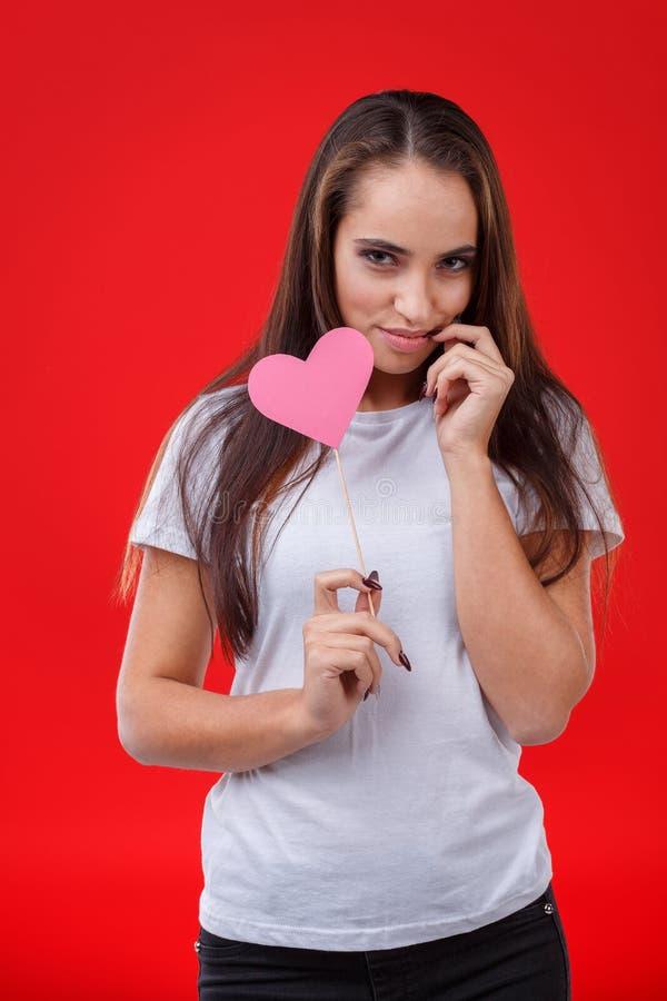 Une jeune fille, supports avec un regard fixe gêné et prises un petit coeur de papier rose sur un bâton photo libre de droits