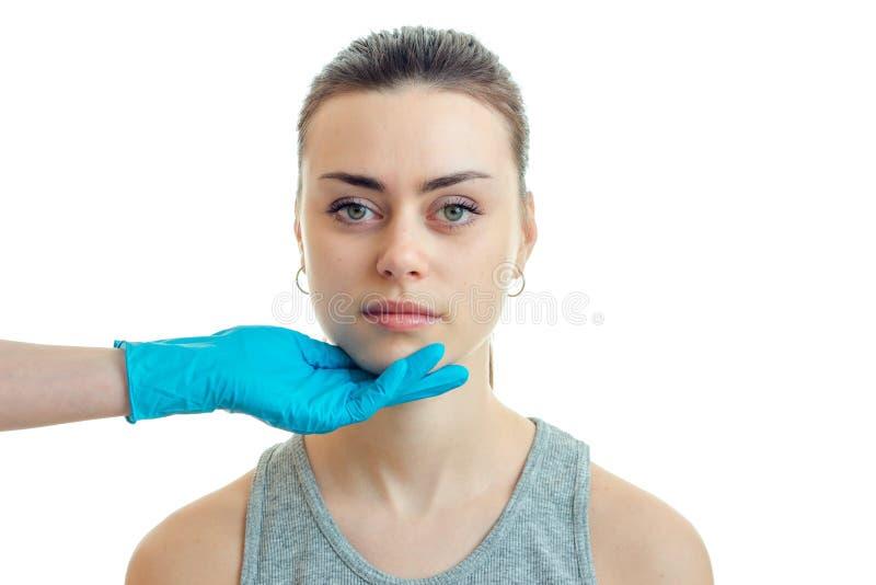 Une jeune fille a tenu Chin dans le gant bleu dans le salon de beauté photographie stock