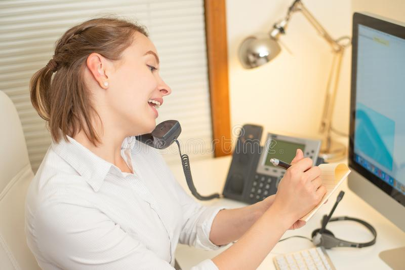 Une jeune fille travaille à un centre d'appels Pour un lieu de travail avec un téléphone Un microphone avec un microphone Service images libres de droits