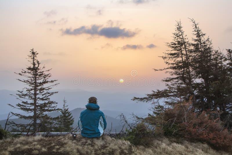 Une jeune jeunesse dans des écouteurs observe le lever de soleil dans les montagnes avec une tasse de thé, un sonception, un voya photographie stock libre de droits