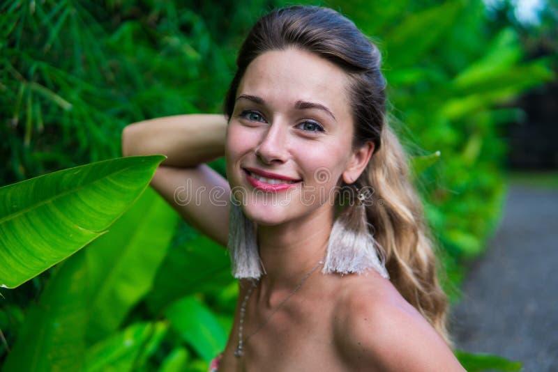 Une jeune jolie femme aux cheveux longs habillée dans une robe marche en parc photos stock